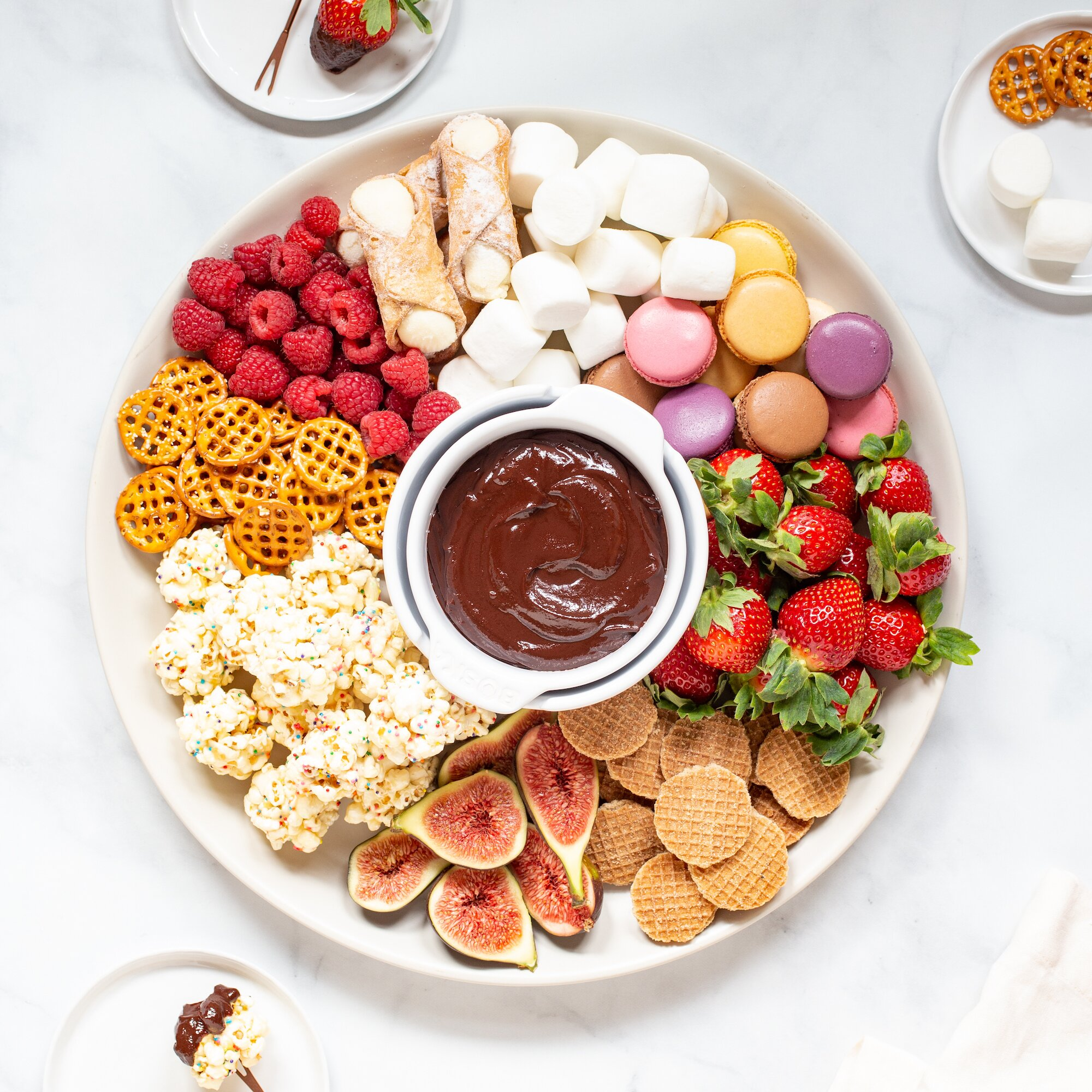 a pot of chocolate fondue with various ingredients for dipping
