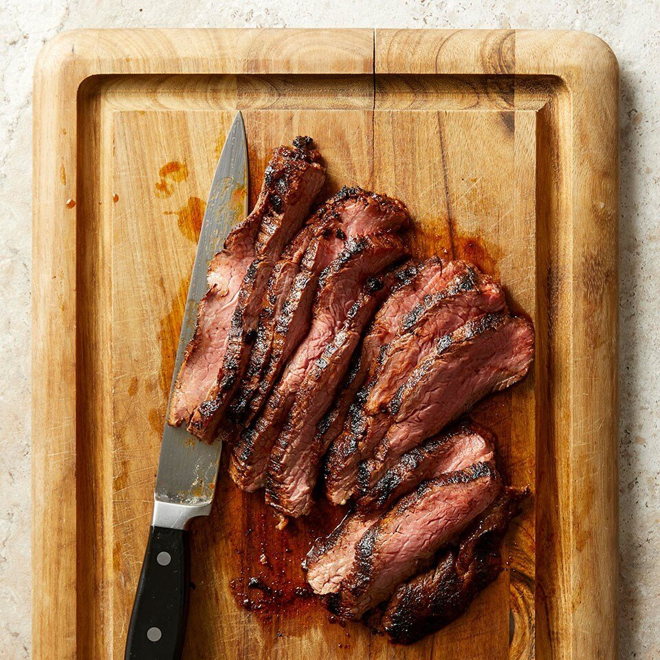 Smoky Grilled Flank Steak on a cutting board