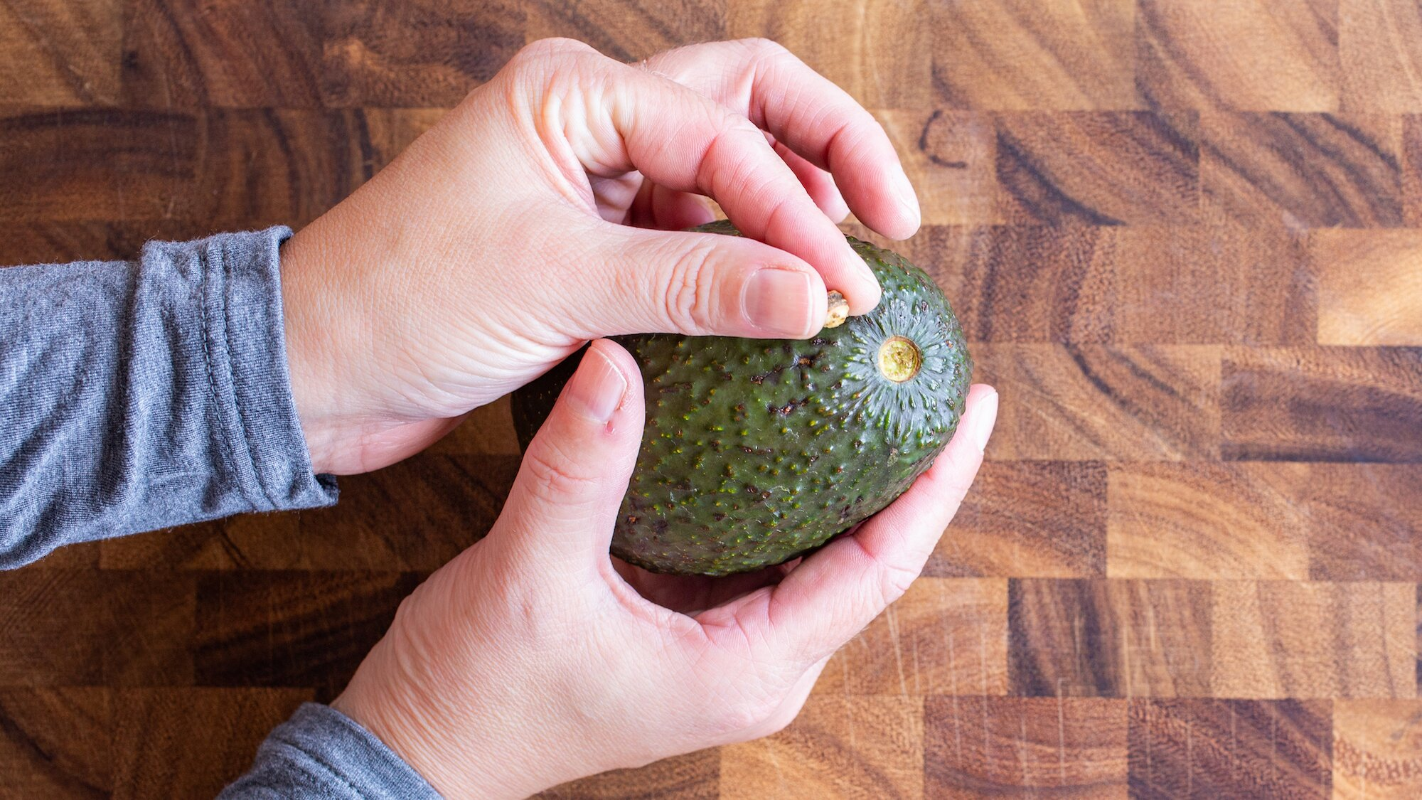 hand holding an avocado, with the other hand holding the avocado stem