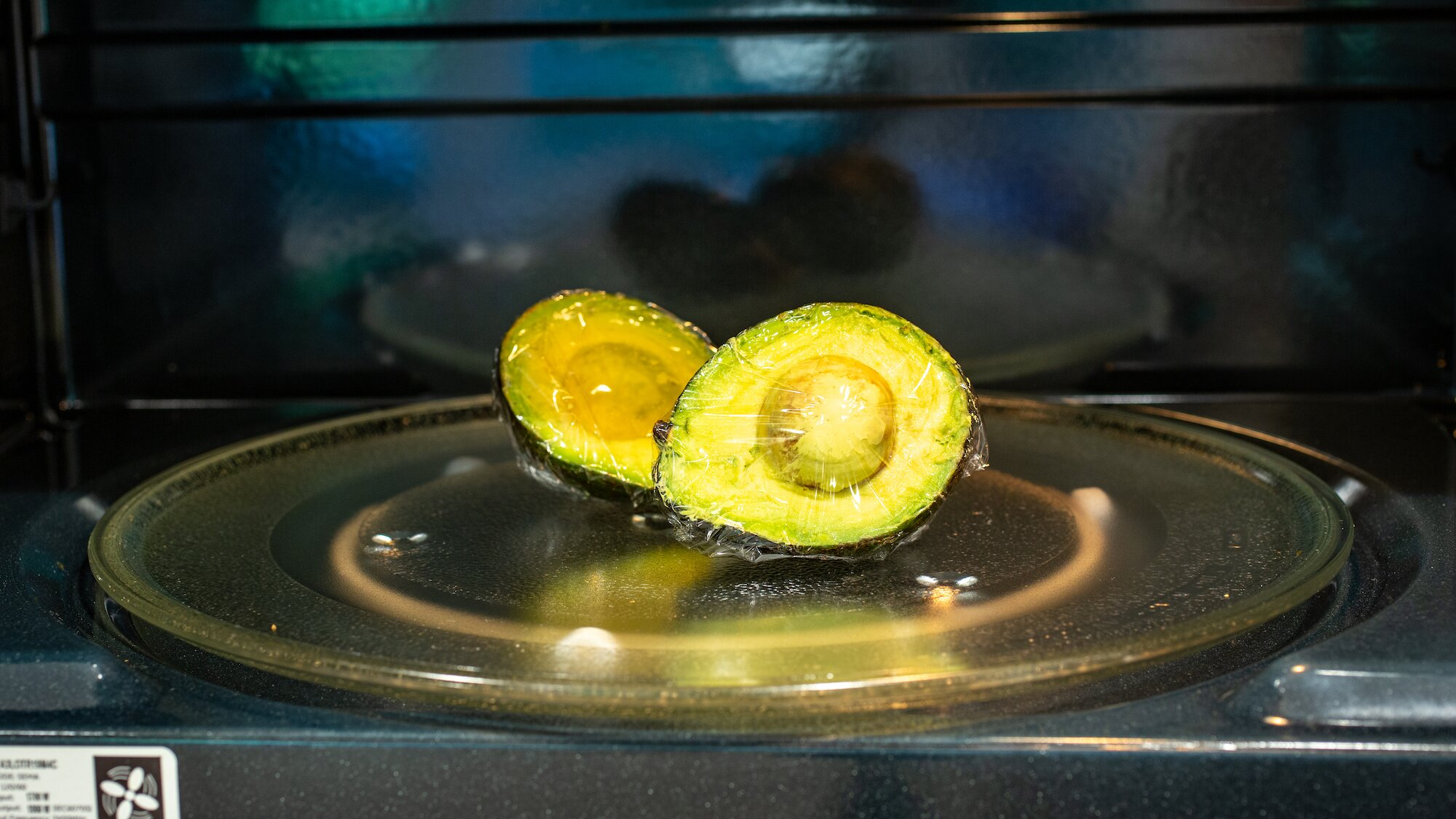 avocado wrapped in plastic wrap in a microwave