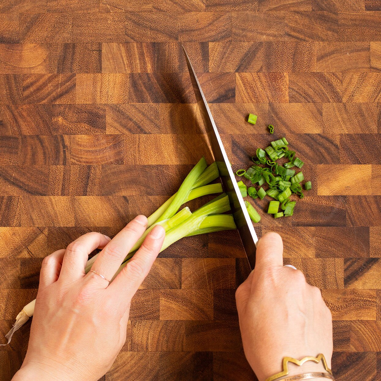 Cutting green onions into round pieces on a wooden cutting board
