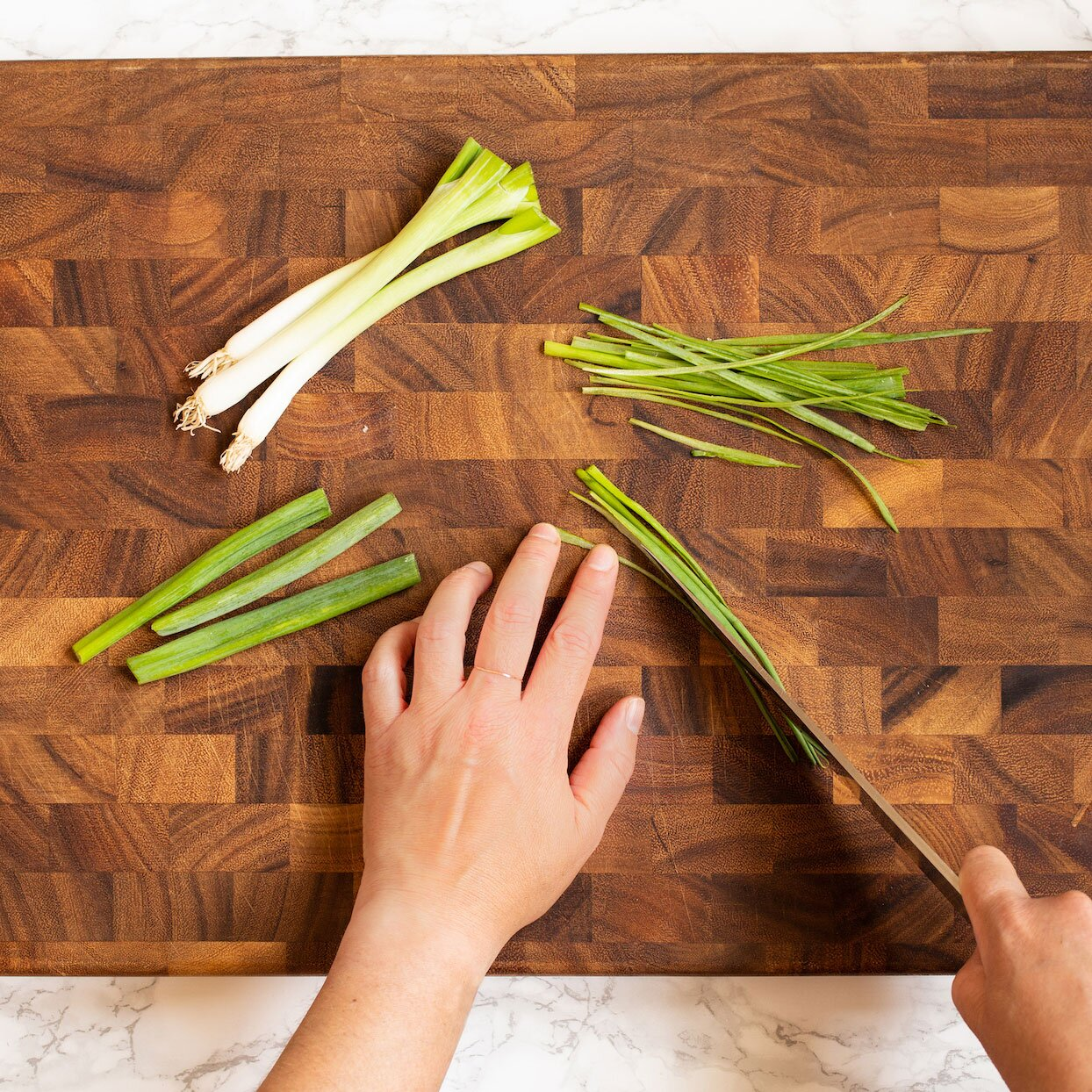 cutting green onions lengthwise on a wooden cutting board