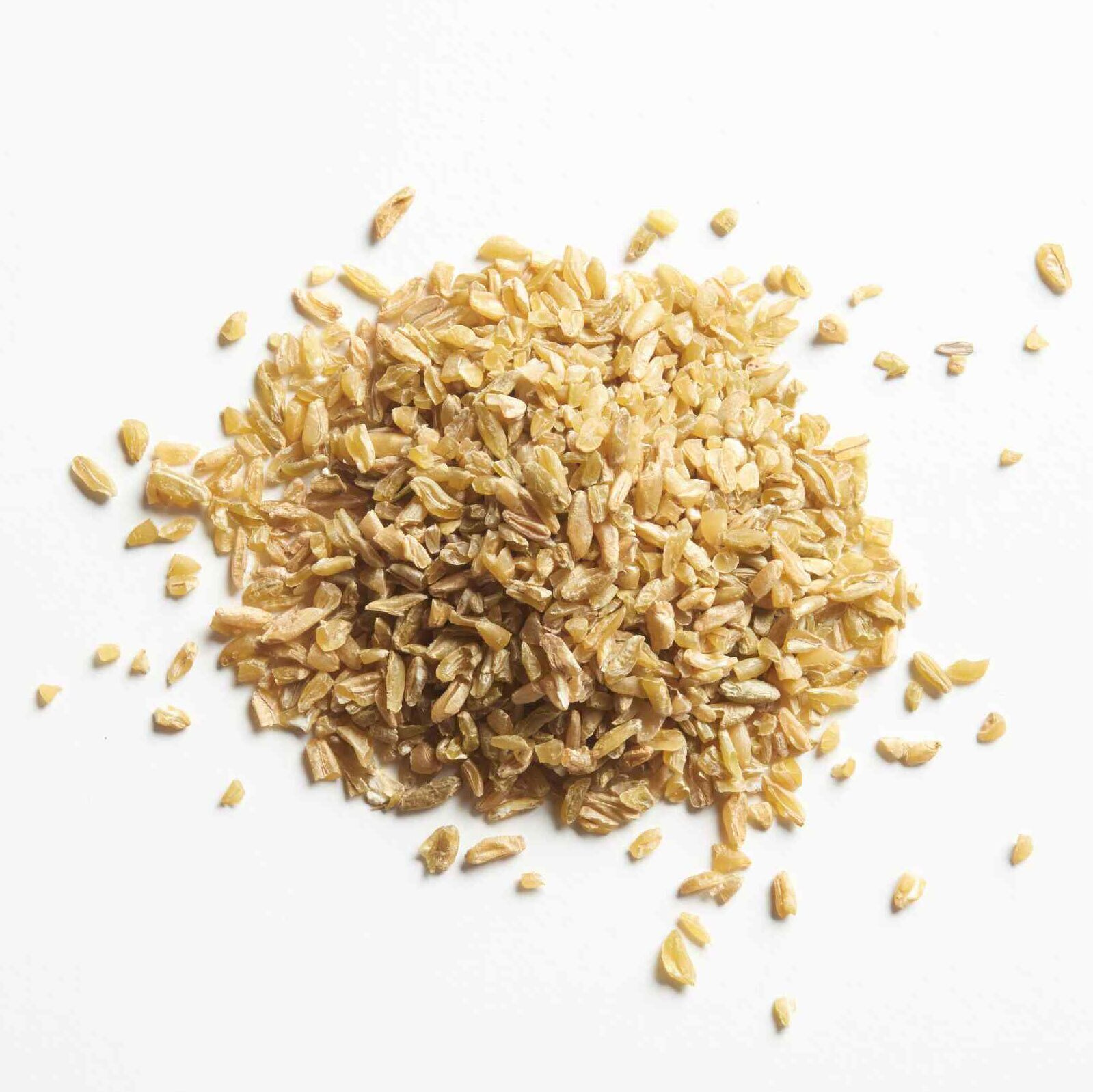 Dried freekeh grains on a white surface.