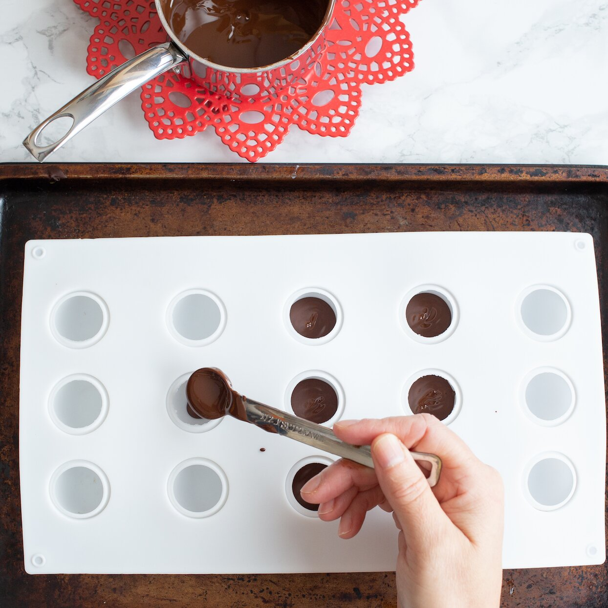 pouring chocolate for hot chocolate bombs