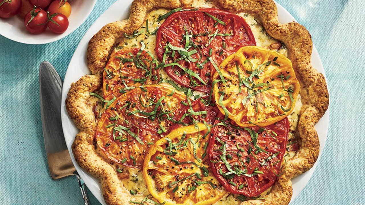 Southern Tomato Pie with red, yellow, and orange tomato slices and strips of basil on top.