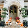 fall porch with large spiders hay and pumpkins