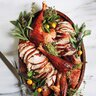 roasted turkey on wooden dish with garnished with oranges and greenery
