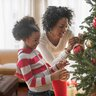 mother and daughter hanging red and gold bulbs on christmas tree