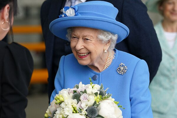 Queen Elizabeth II receives flowers as she meets employees during a visit to AG Barr's factory in Cumbernauld