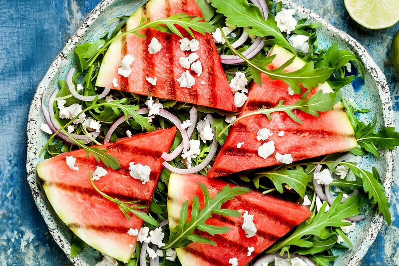 grilled food ideas: Fresh summer grilled watermelon salad with feta cheese, arugula, onions on blue background