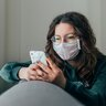 Woman wearing face mask while using phone