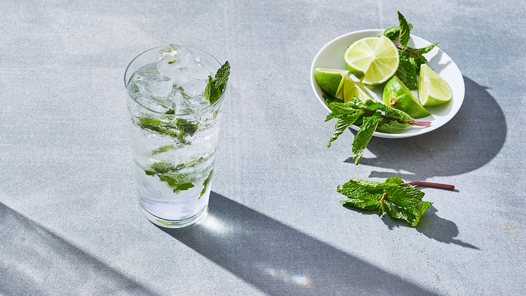 a mojito next to a dish of lime wedges and mint
