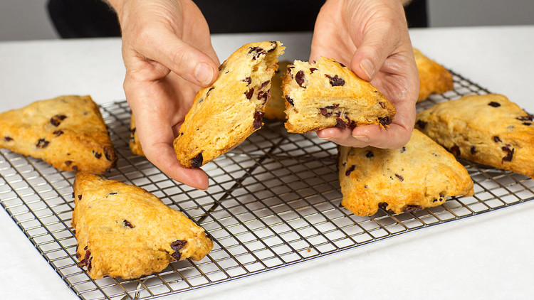 hands holding flaky cranberry scones