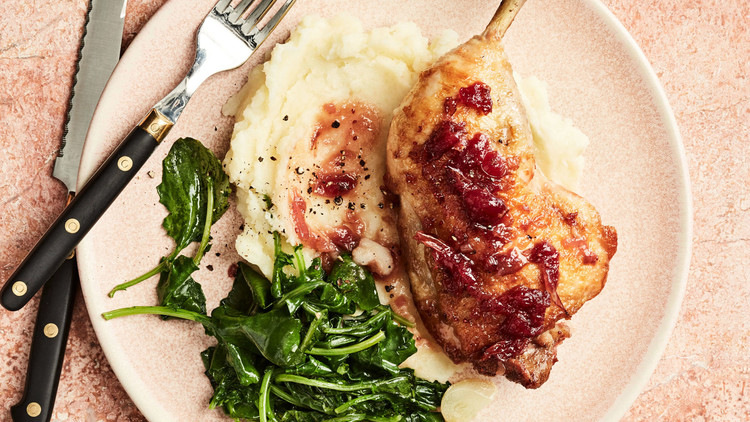 cranberry chicken with greens on plate with cutlery