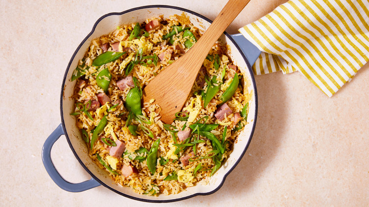 ham and snow-pea fried rice in a white and blue pot with a wooden spoon