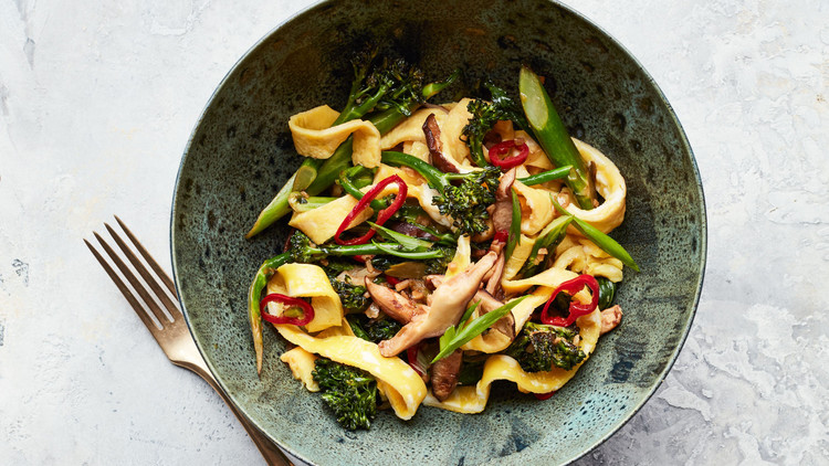 egg noodle broccolini and mushroom stir fry served in green bowl