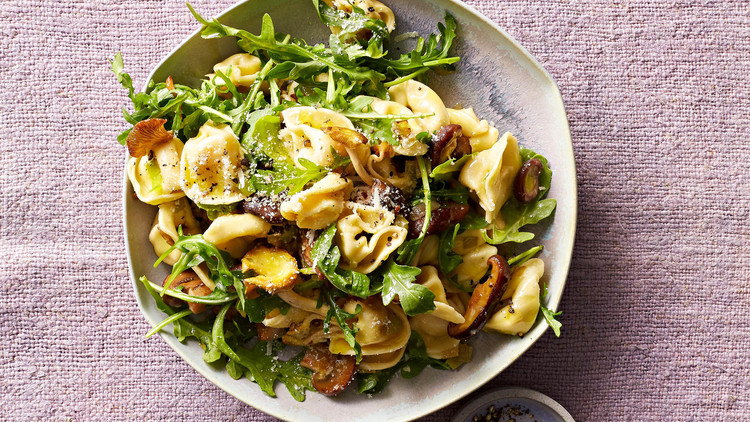 mushroom tortellini with arugula on plate