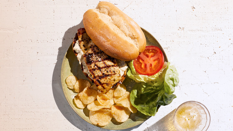 grilled salt-rubbed fish sandwich served with chips