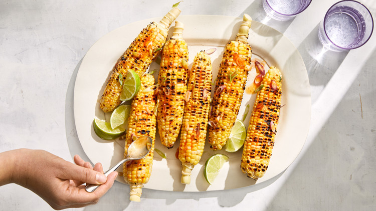 grilled corn with fish sauce and scallions served with lime wedges