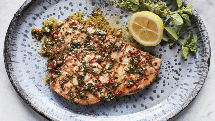 swordfish with sicilian oregano-caper sauce served on a blue speckled plate