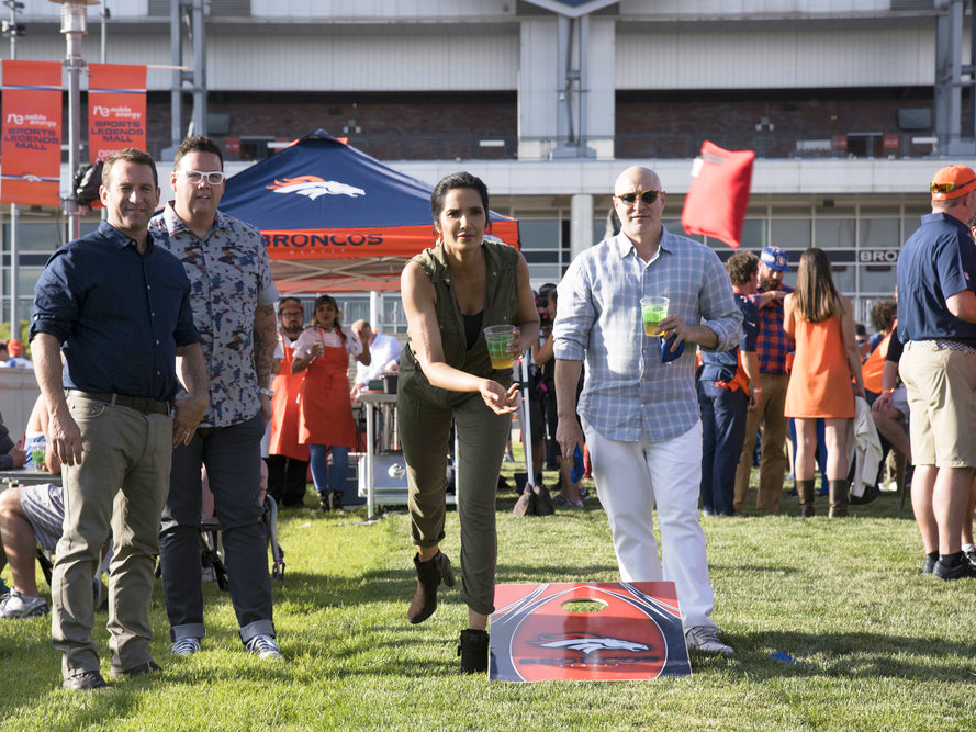 Padma and Tom play cornhole at Mile High stadium.