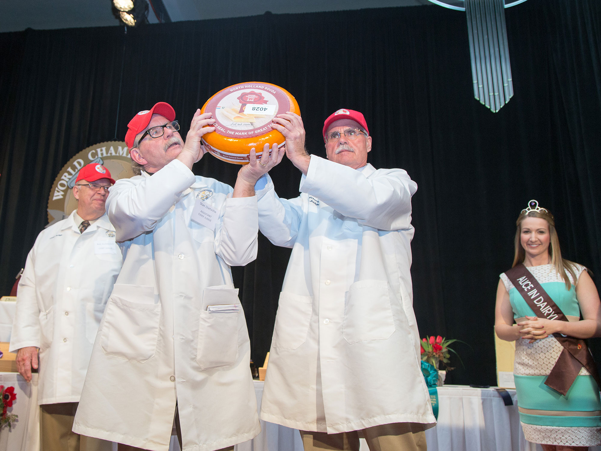 Jim Mueller (right) holding up a winning cheese from the contest with another Assistant Chief Judge, Stan Dietsche