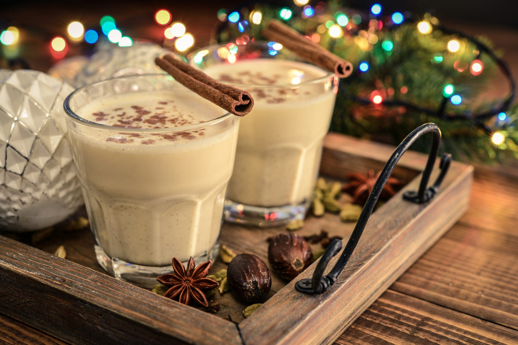 Traditional Christmas eggnog in glass with spices and Christmas lights on a wooden serving tray.