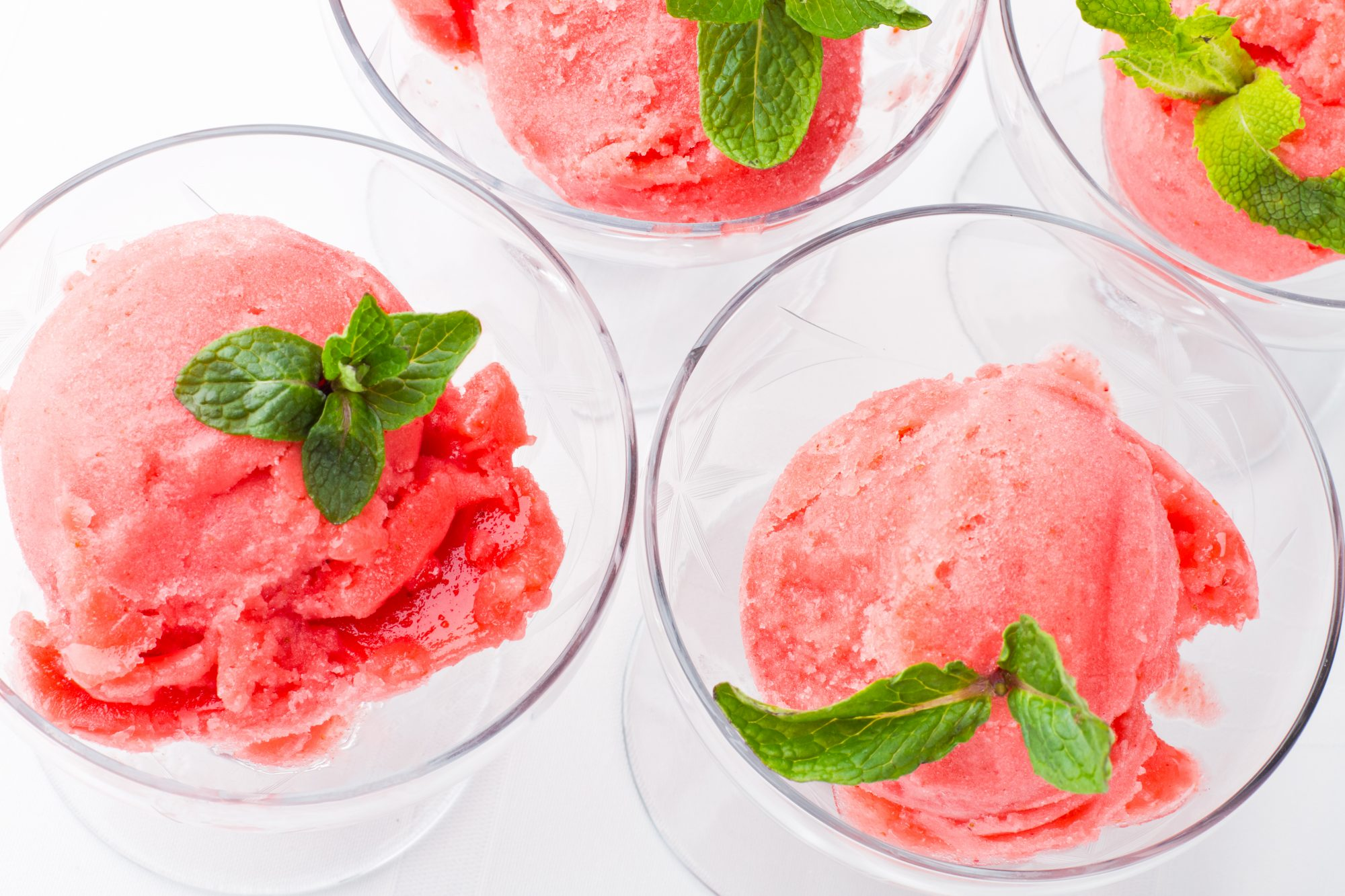 Raspberry sorbet scooped into glasses and topped with fresh mint