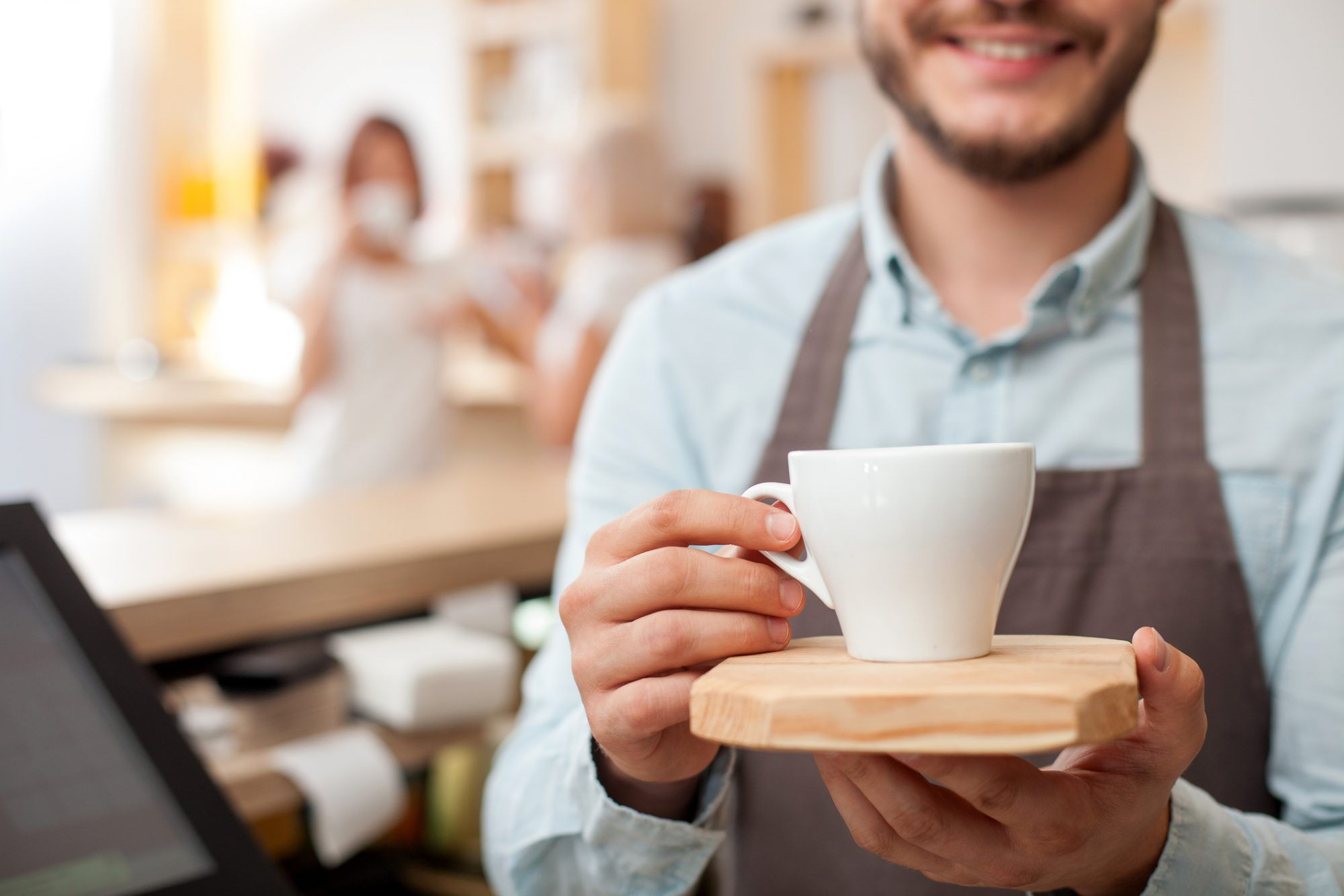 Close up of worker of cafeteria. The man is holding a cup of coffee and giving it with joy. The man is standing and smiling. Two women are drinking espresso and talking on background