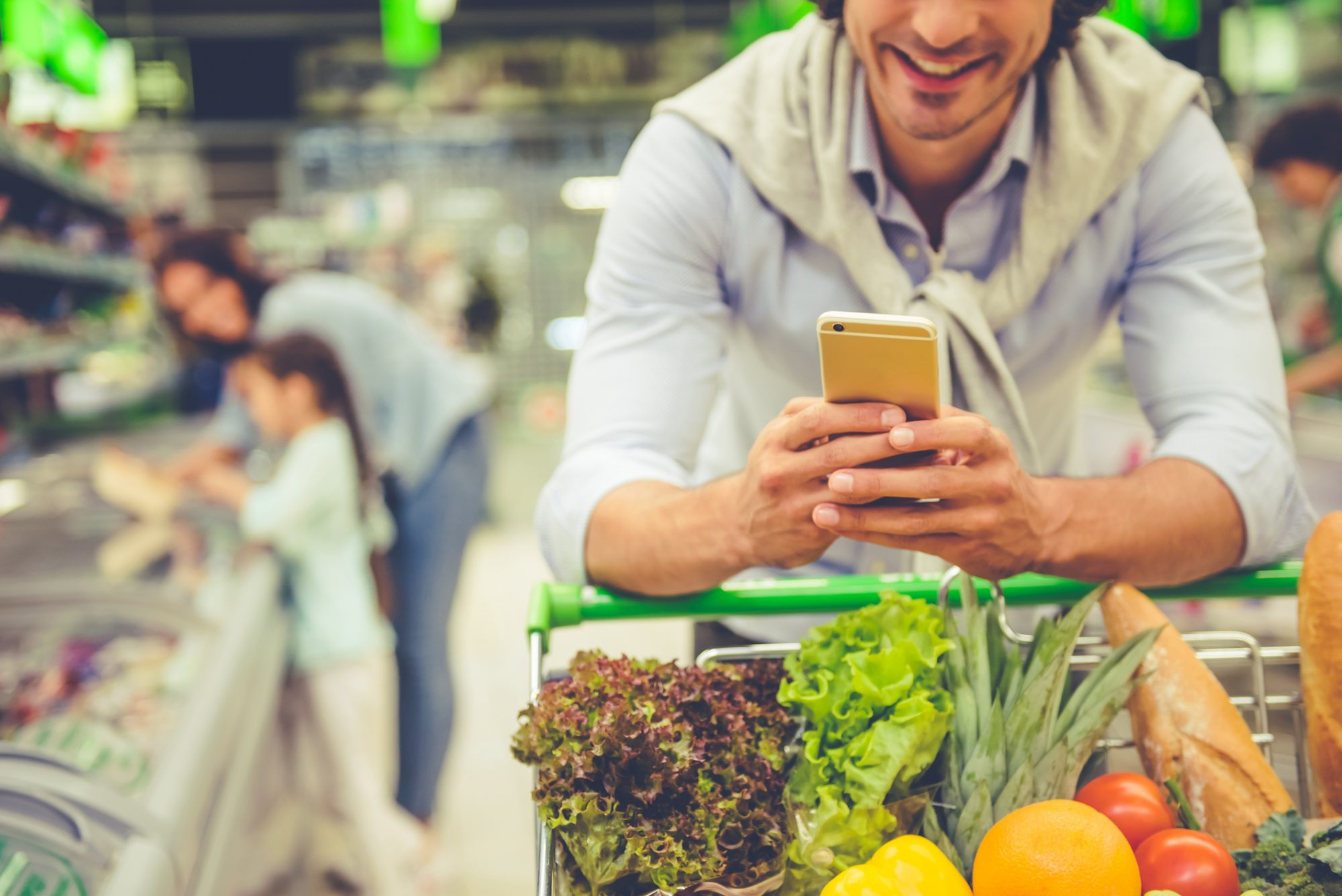Family in the supermarket. Cropped image of dad leaning on shopping cart, using a mobile phone and smiling, in the background his wife and daughter are choosing food
