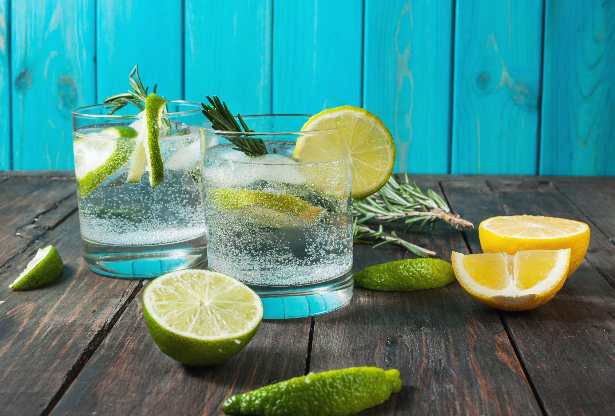 Alcoholic drink gin tonic cocktail with lemon, rosemary and ice on rustic wooden table, copy space