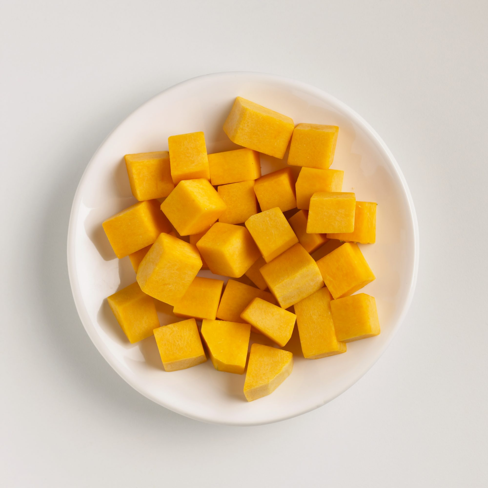 Cubed pumpkin on a white plate.