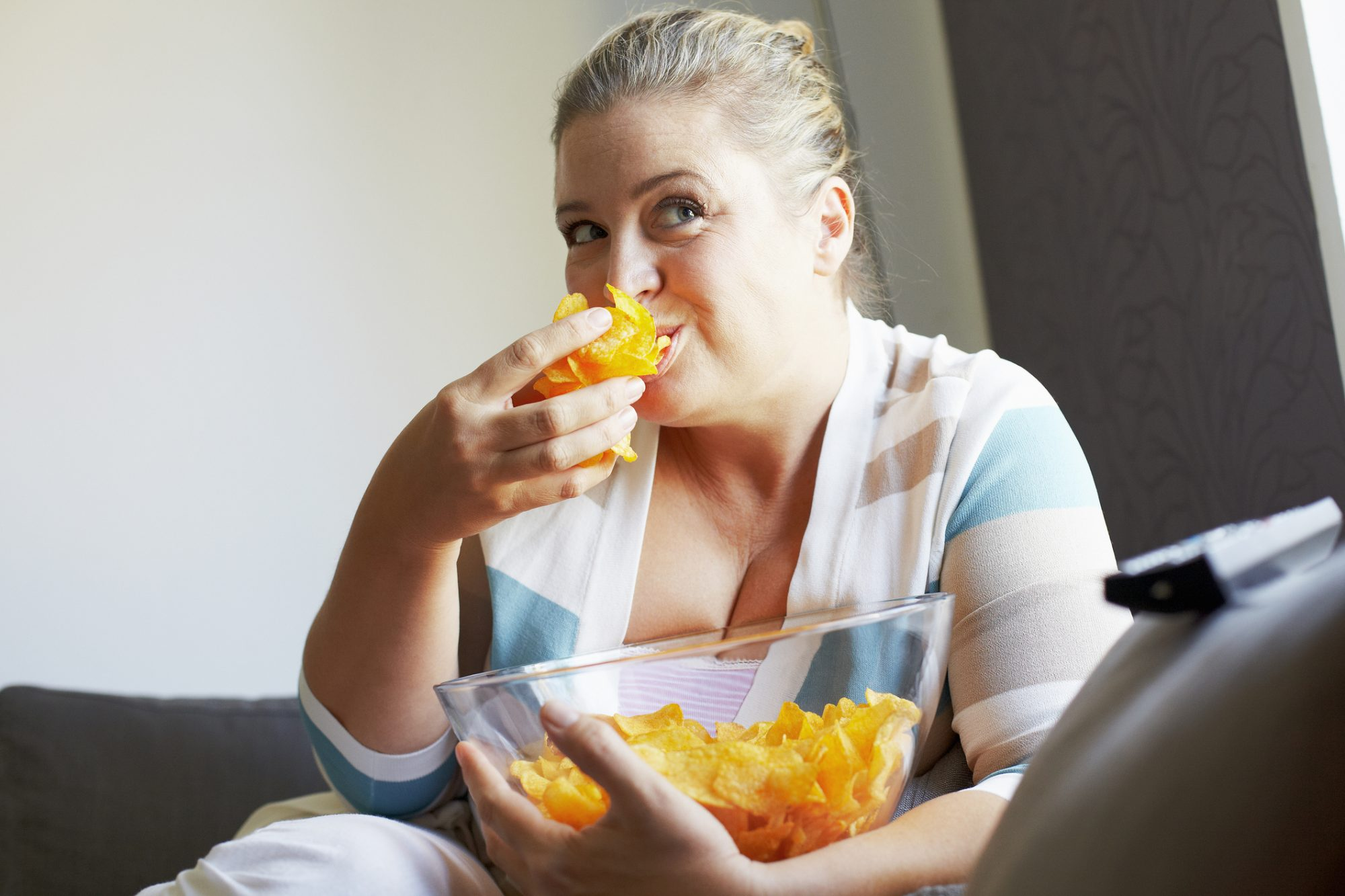 Smiling woman eating chips on sofa