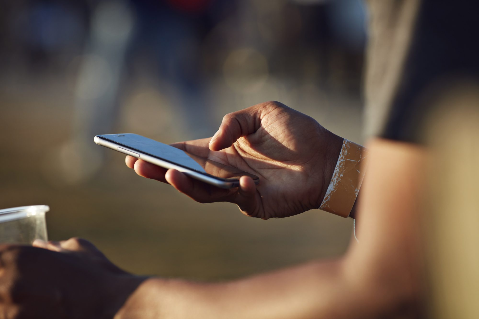 Close-up of hand scrolling on phone at festival