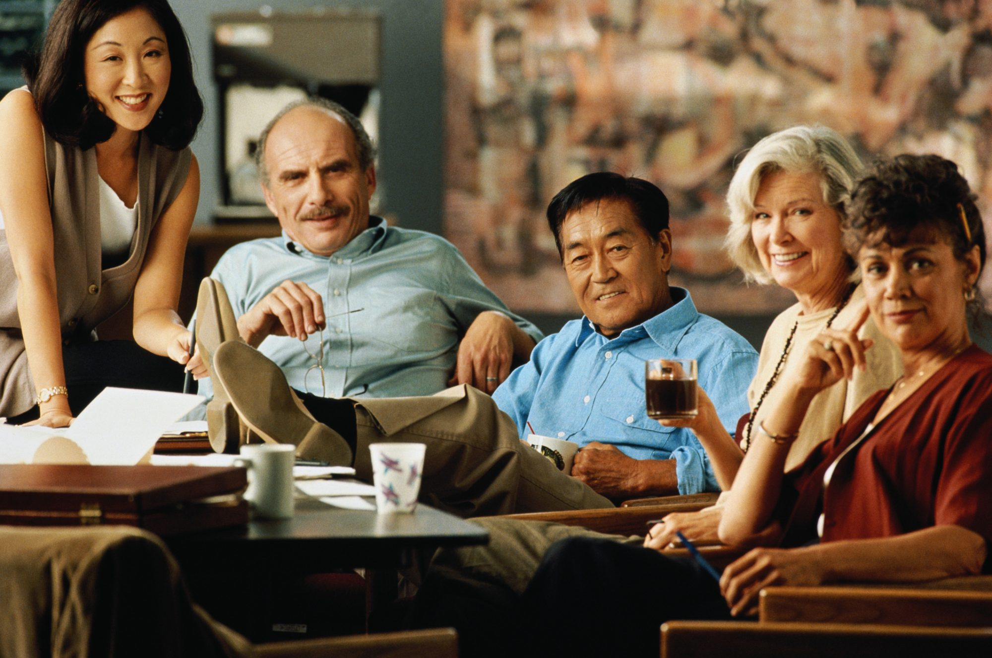 Group of business executives sitting around table, portrait