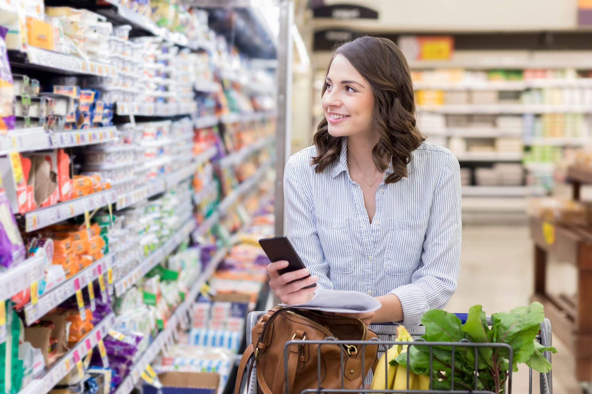 Woman Grocery Shopping with Phone Out