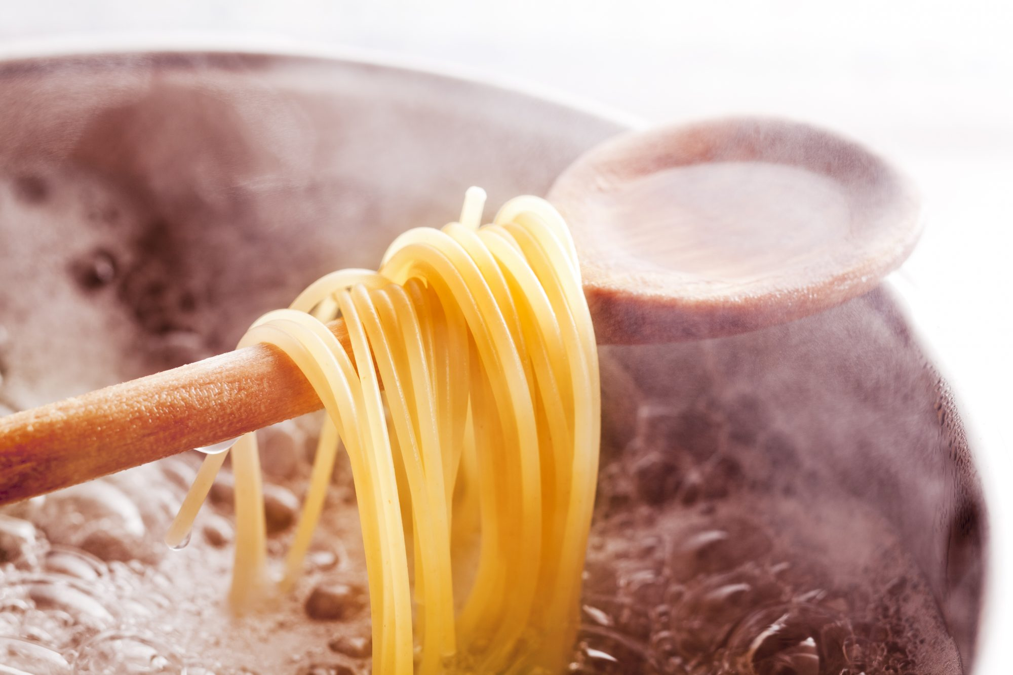 Spaghetti strands on a spoon above boiling water
