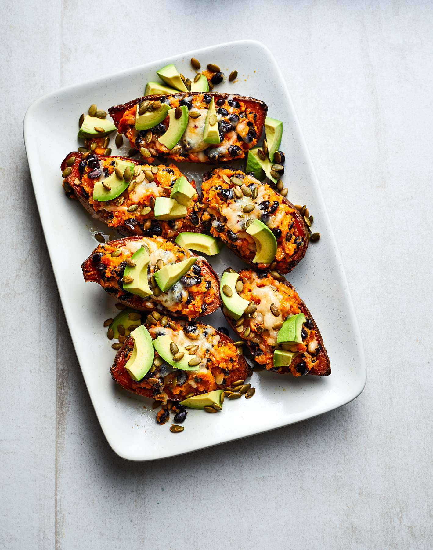 Cheesy Twice-Baked Sweet Potatoes With Black Beans and Avocado