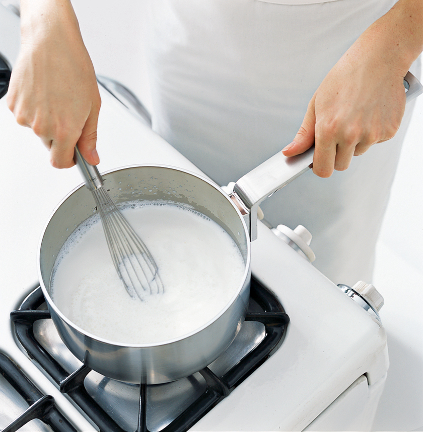 Woman frothing milk in a saucepan