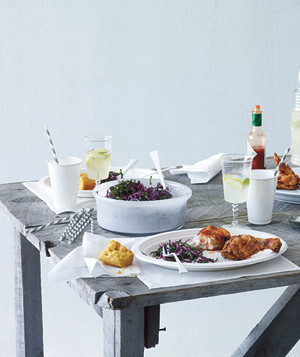 Picnic table set with with fried chicken, slaw and lemonade
