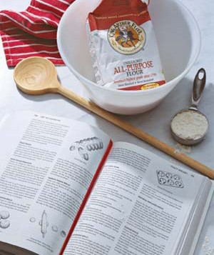 Cookbook, flour, and spoon