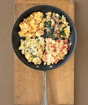 Four versions of scrambled eggs in pan