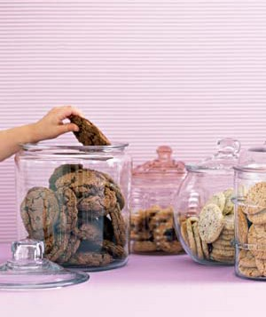 Child taking cookie from cookie jar