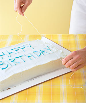 Woman slicing a sheet cake with dental floss