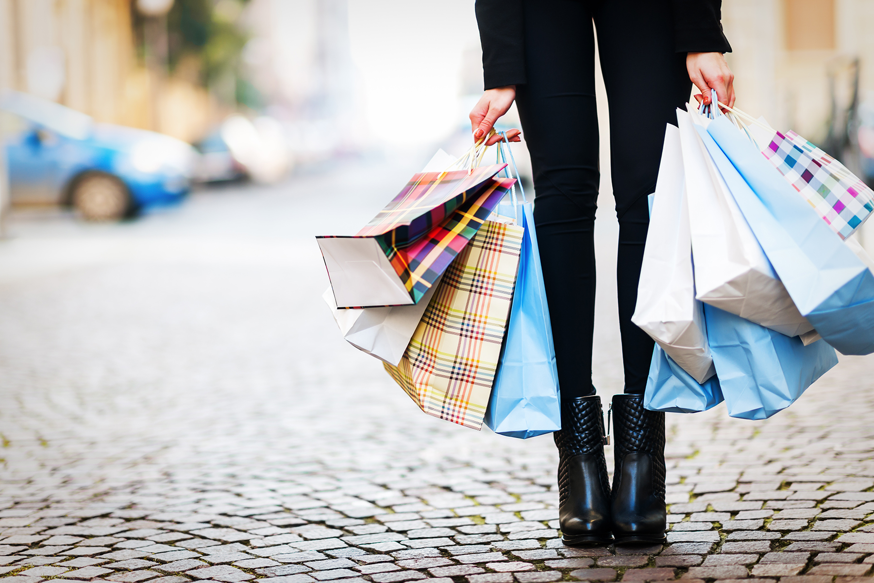 Woman wearing black leggings and boots carrying shopping bags