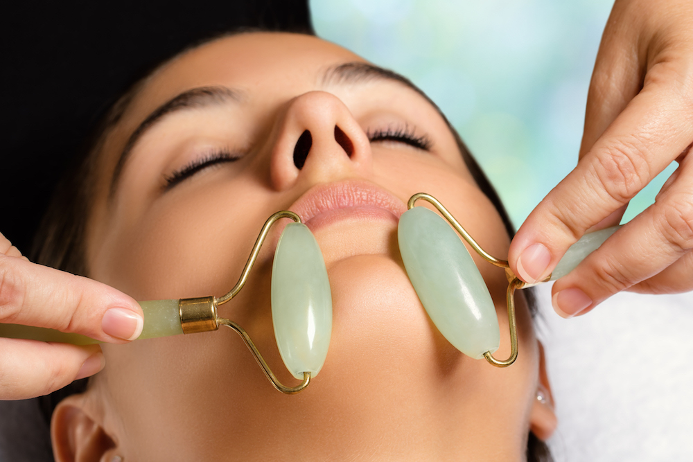 A Woman Getting Her Skin Treated With Jade Rollers