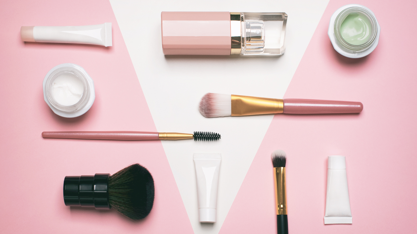 Grouping of makeup on a pink background