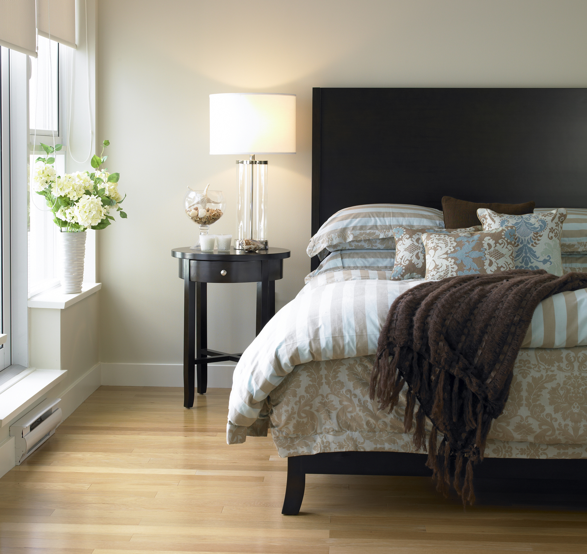Bedroom with brown and blue bedding, bedside table, flowers