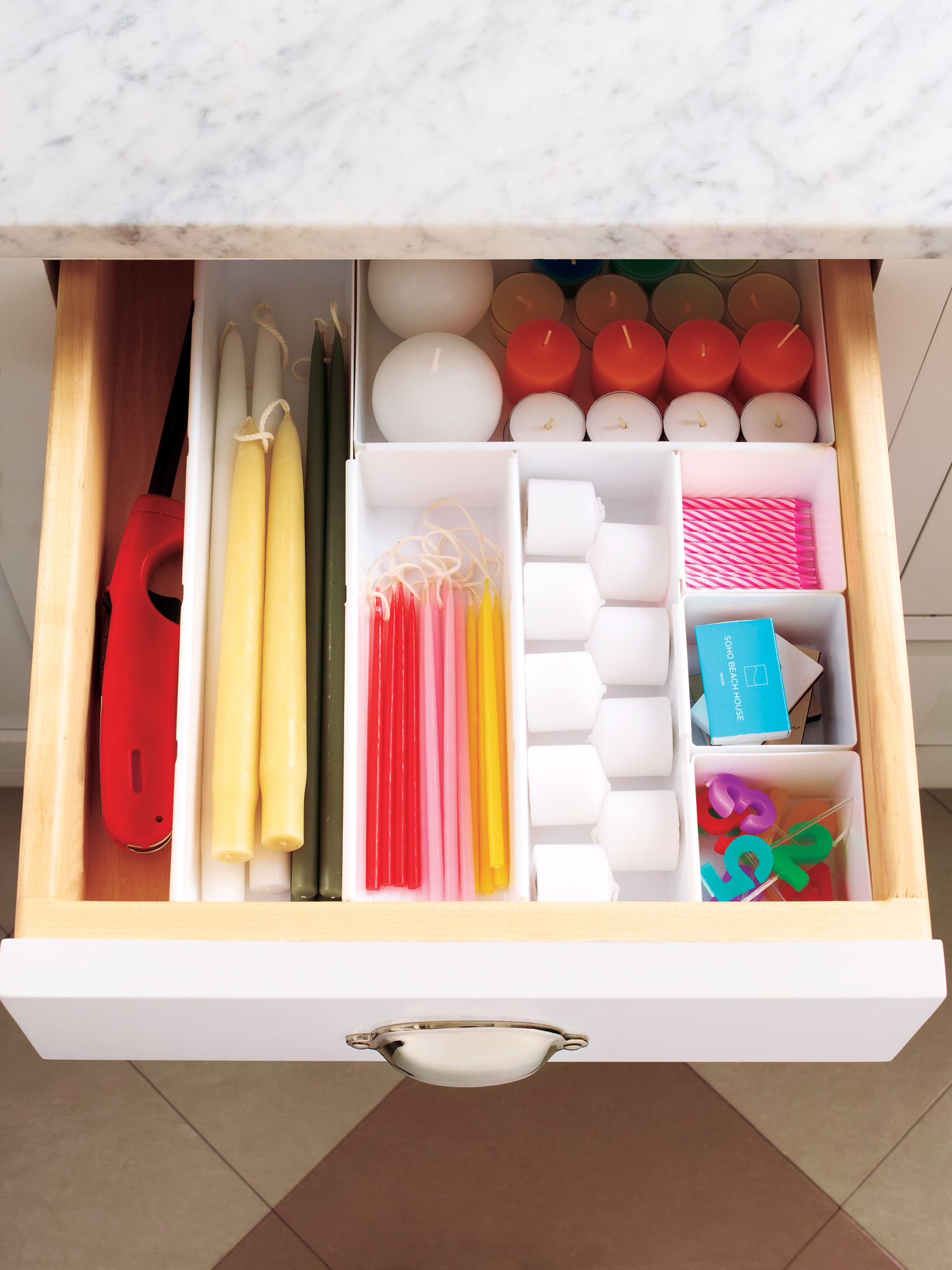 Candles, matches, and lighter organized in a drawer
