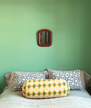 Bedroom with painted green wall, small mirror and bed without headboard